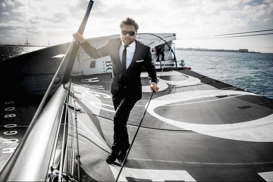 In a daredevil feat, the British yachtsman scales the 60-foot mast of the HUGO BOSS and dives into the ocean wearing a BOSS formal suit